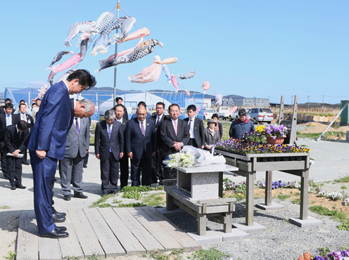 "Photograph of the Prime Minister offering a silent bow in front of the ""Ganbaro! Ishinomaki"" signboard"