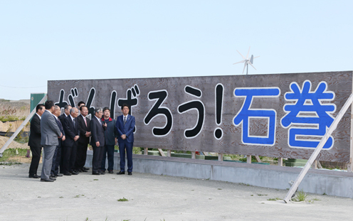 "Photograph of the Prime Minister observing the ""Ganbaro! (Let's do our best) Ishinomaki"" signboard"