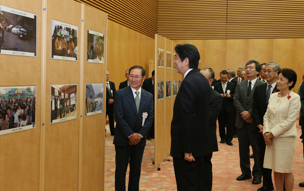 Photograph of the Prime Minister receiving an explanation on the state of activities while viewing a display panel.
