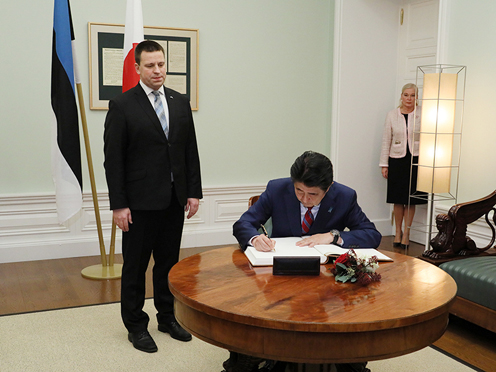 Photograph of the Prime Minister signing a book prior to the summit meeting