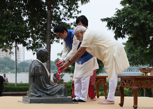 Photograph of both leaders offering flowers at a statue of Mahatma Gandhi
