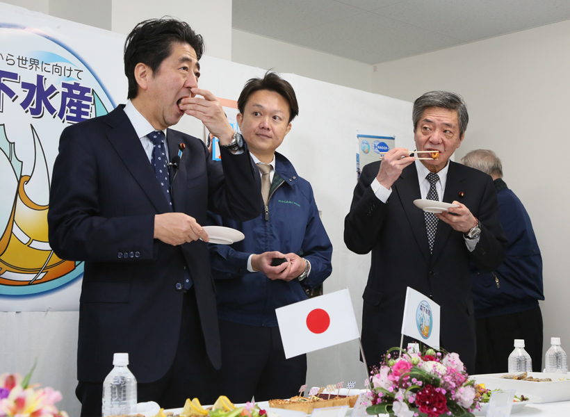 Photograph of the Prime Minister sampling fishery processing plant products
