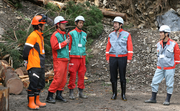 Photograph of the Prime Minister exchanging views with workers from the Nakahechi Town Forest Union conducting forest thinning