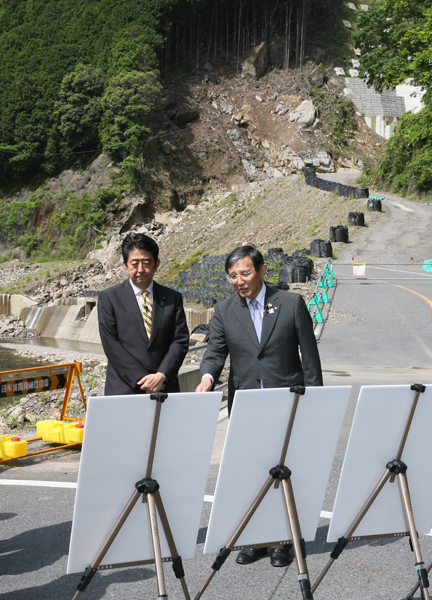 Photograph of the Prime Minister receiving an explanation from Governor Nisaka of Wakayama Prefecture on the state of repairs of National Route 311 at a section damaged by a natural disaster