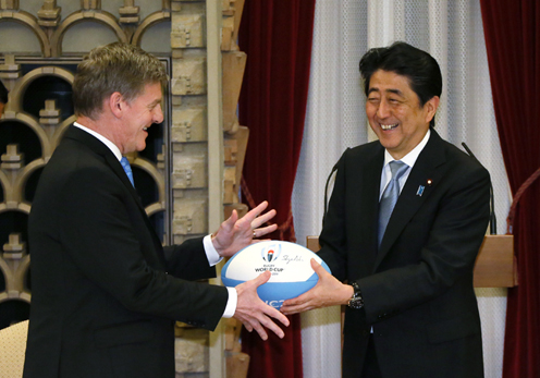 Photograph of the Prime Minister presenting a ball to commemorate the Rugby World Cup at the banquet hosted by Prime Minister Abe and Mrs. Abe