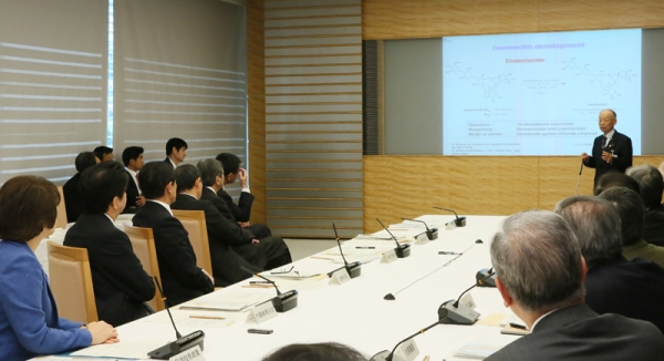 Photograph of the Prime Minister listening to the explanation by Professor Emeritus Satoshi Omura