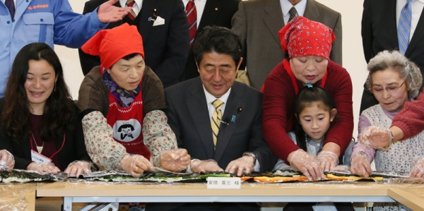 Photograph of the Prime Minister making jumbo seaweed rolls with other participants at an assembly hall