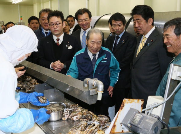 Photograph of the Prime Minister observing oyster shucking