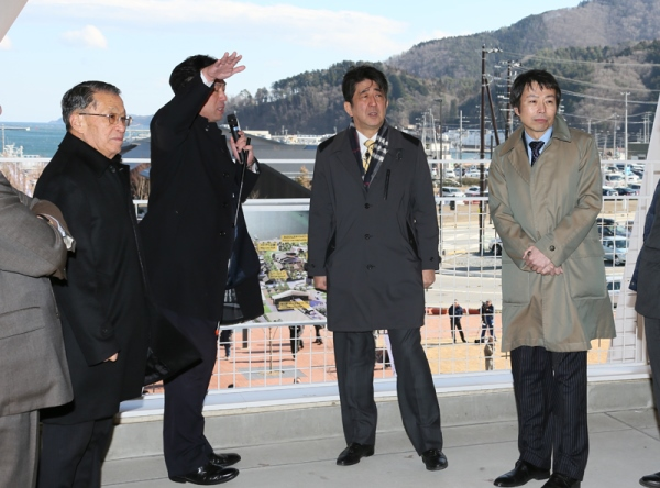 Photograph of the Prime Minister receiving an explanation about the progress of reconstruction from the Mayor of Onagawa Town at the observation deck on the roof of the new train station