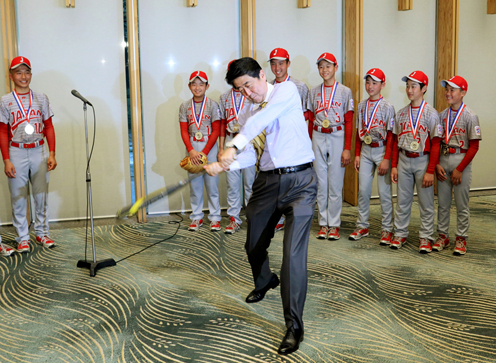 Photograph of the Prime Minister swinging a bat