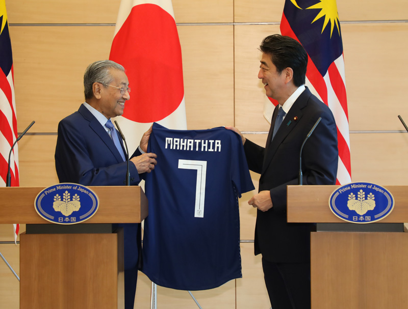 Photograph of the Prime Minister presenting a uniform of the Japan national soccer team