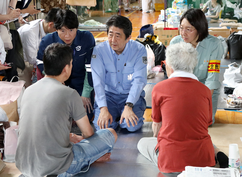 Photograph of the Prime Minister listening to those affected by the disaster