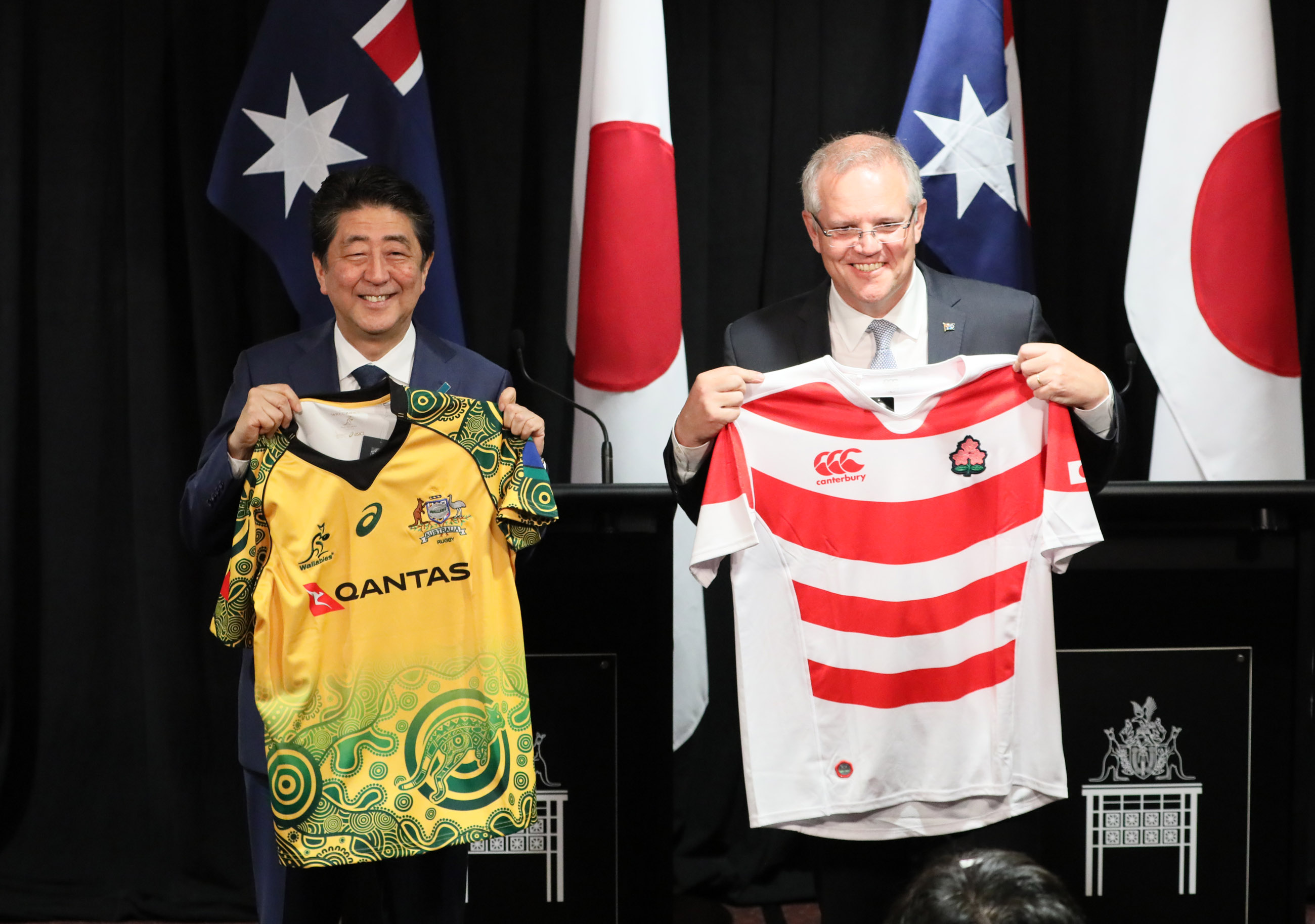 Photograph of the leaders exchanging national rugby jerseys