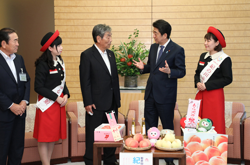 Photograph of the Prime Minister being presented with the peaches