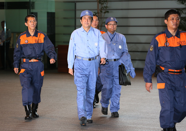 Photograph of the Prime Minister leaving the Prime Minister's Office in disaster prevention gear