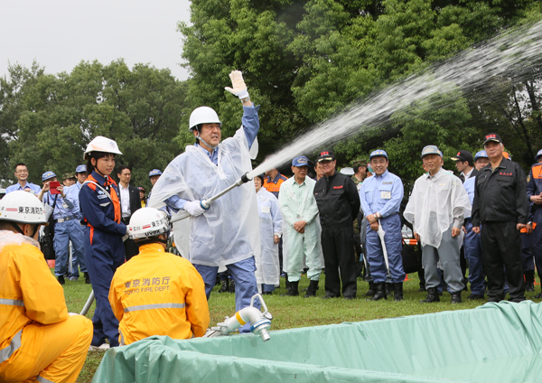 Photograph of the Prime Minister participating in the firefighting drill using a standpipe fire hose