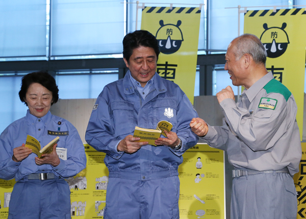 Photograph of the Prime Minister being presented with a disaster prevention book from the Governor of the Tokyo Metropolitan Government