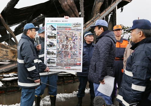 Photograph of the Prime Minister receiving an explanation at the area affected by the fire