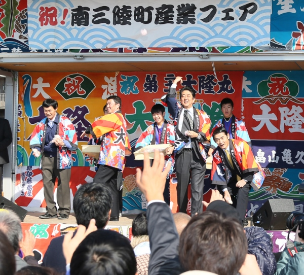 Photograph of the Prime Minister passing out mochi rice cakes at the Minamisanriku Town Industrial Fair